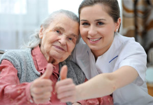 senior women and female nurse are showing thumbs up